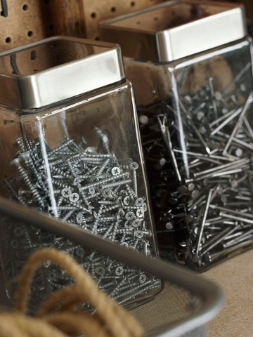 Clear glass kitchen canisters work as well in the garage or workshop as they do in the kitchen. Use them to store screws, nails, and other hardware that often gets lost in the backs of drawers or the bottom of a toolbox.