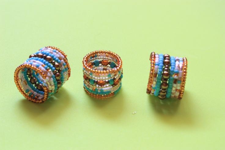 Geo Ecléctica. Diseño de Anillos en alambre de memoria, hecho con mostacillas y cristales checos, colores turquesa, dorado, rojo, beige y perla.