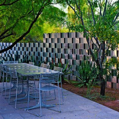 """""""Steve Martino wove aluminum flashing through rebar uprights like a ribbon, creating a glamorous shimmering privacy wall near the outdoor dining area."""" Sunset Magazine"""