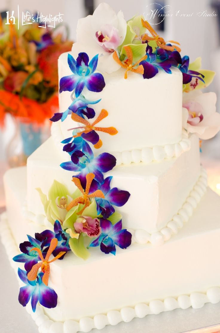 Simple Buttercream Wedding Cake With Fresh Blue Green And Orange Orchids Cascading Down The