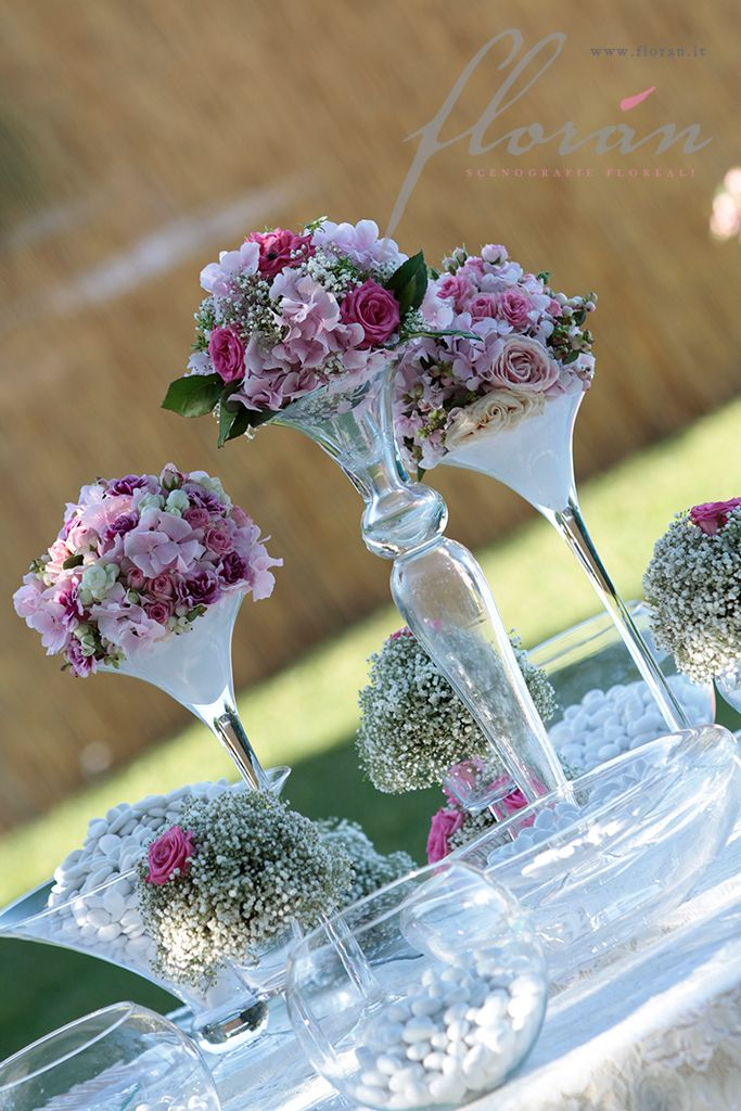 Tall vase centerpiece surrounded by smaller arrangements of baby's breath