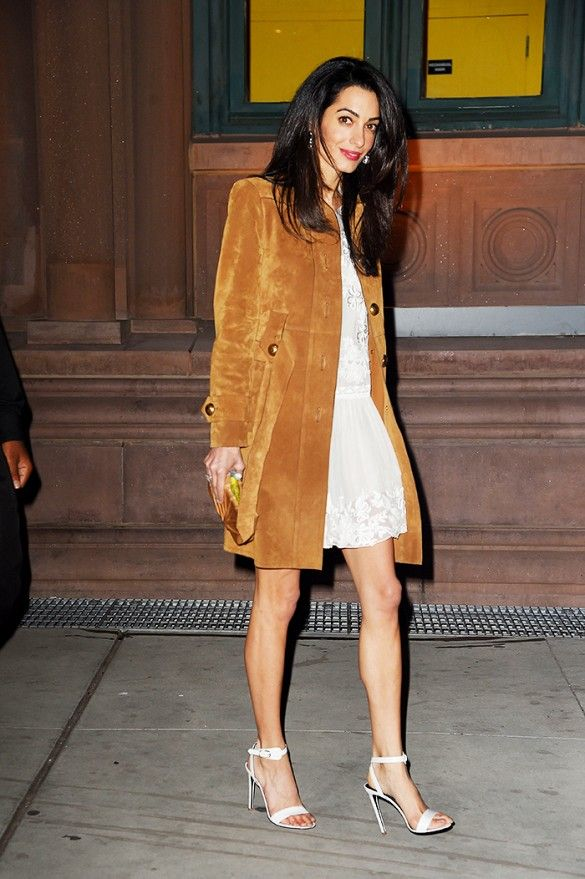 Amal Clooney in a white lace dress, white heeled sandals, and a suede coat