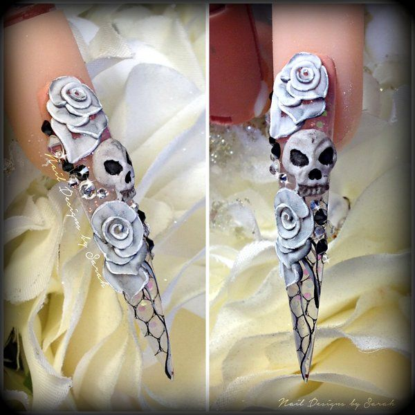 hand made 3D skulls and roses on a stiletto nail with real net encapsulated in the stiletto