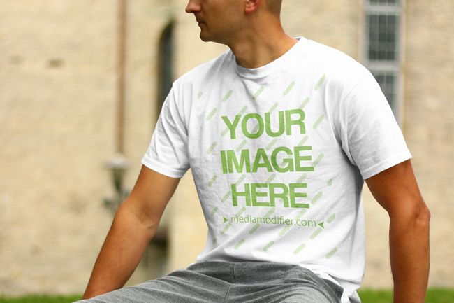Online mockup scene with a young white male model sitting on a park bench in summertime. Upload your own custom design on the blank round neck shirt and generate a preview within seconds. Online t-shirt front view mockup generator with a young man sitting outdoors.