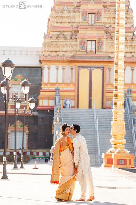This pretty South Indian couple posing in front of the temple! www.wittyvows.com