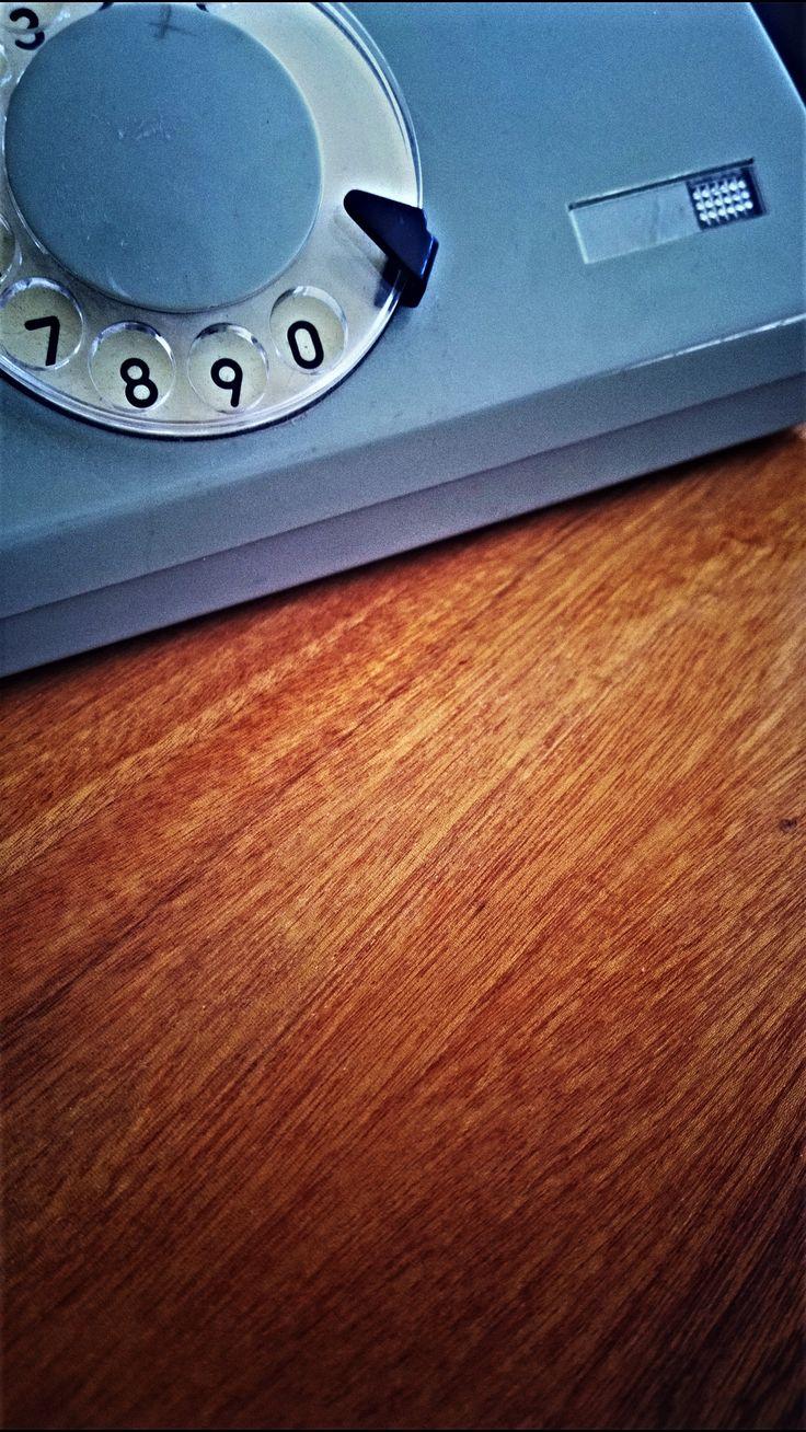 Połyskliwy fornir polskiego stolika z lat 60. i ebonitowy telefon, z którego dzieci nie potrafiłyby już nigdzie zadzownić