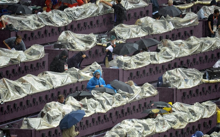 Members of the media protect their equipment with rain covers during the athletics in the UK Olympic Stadium
