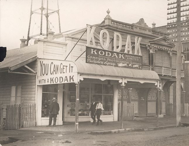 Black and white photograph of a Kodak Australasia Ltd shop in Townsville, Queensland, circa 1911 - 1920. They are situated next to the Townsville fire station. This store also promotes the sale of records as well as cameras and photographic supplies. A man is looking at a window display of gramophones. Townsville, Queensland