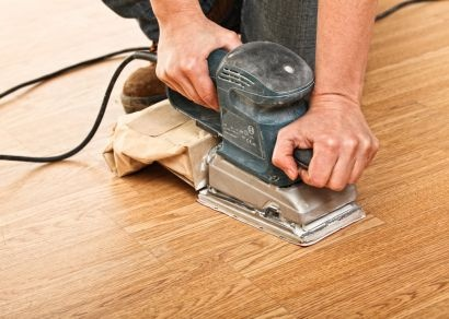 Here are a few tips on how to refinish oak floorsSanding a wood floor image via Shutterstock.