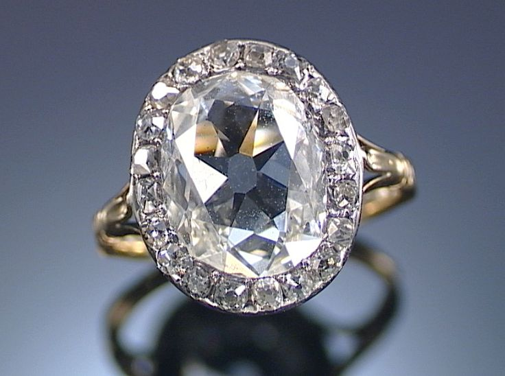 DIAMOND RING, EARLY 19TH CENTURY. Centring on an oval diamond within surrounds of single-cut stones