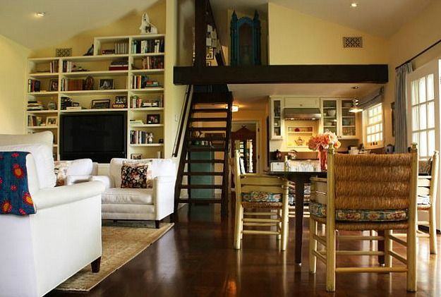 TV behind low back chairs and built into bookshelves, staircase to loft area, lower kitchen ceiling defines space in open concept.