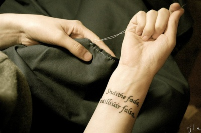 """Gaelic on the wrist that says """"All that is gold does not glitter, Not all those who wander are lost"""""""