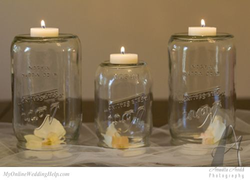 Front view, upside down mason jars with candles on top.