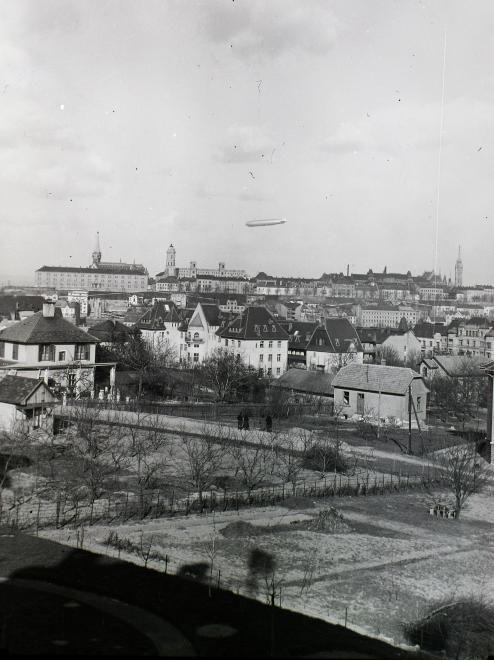 előtérben az Ügyész utca, szemben a Kék Golyó utca házsora, felette a budai Vár és a Graf Zeppelin léghajó.