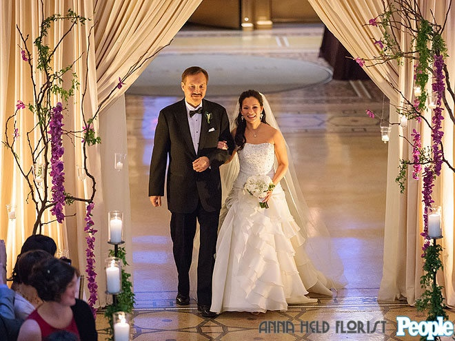 The Amazing Race Winners, Cindy and Ernie, were wed at Chicago's Rookery Building. The aisle was treated with orchids hung from bare branch trees. Image courtesy People Magazine. Styled by Anna Held Florist, Chicago.