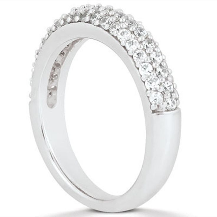 Three rows of pave diamonds enliven this expertly crafted 14K white gold wedding band. The ring is set half way across with diamonds. The look is bold and glamorous.