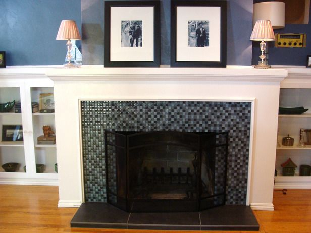 The brick is covered with a glass-tile surround to give the fireplace a modern look. Glass cabinet doors installed on shelves provide the space with a quaint cottage style.