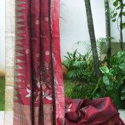 Maroon Khadi silk with zari dots on the body and a zari border lined with temples. The pallu has a random arrangement of flowers with the same flowers placed seemingly randomly on the body