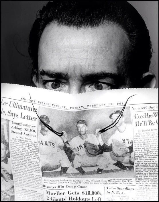 """""""Salvador Dali photographed by © Philippe Halsman, 1954."""" -- He and his mustache are reading...and decorating...the paper."""