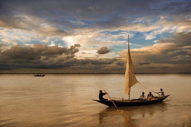 M. J. Hasan, un fotograf amator din Bangladesh, a fotografiat o calatorie cu barca pe Raul Padma, Kushtia. Acesta a surprins perfect peisajul aproape monocrom, in care singura pata de culoare vesel...
