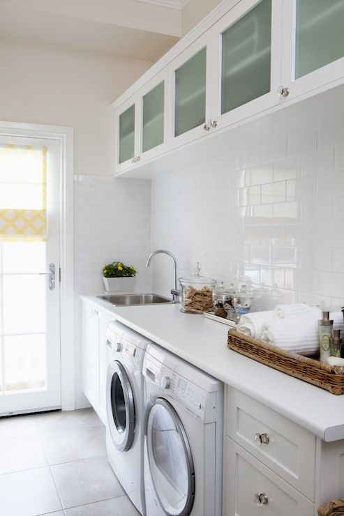long, thin laundry room. white on white. love the glass tile back splash
