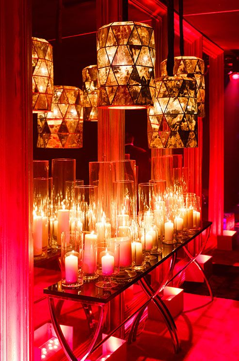 The light from countless hurricanes with pillar candles is dramatized by a large wall mirror.