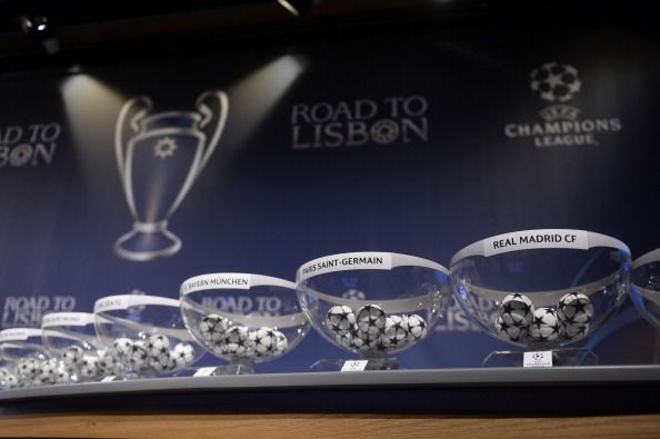 Draw balls with the names of the teams sit on a table at the start of the draw for the last 16 of the UEFA Champions league tournament at the UEFA headquarters in Nyon on December 16, 2013