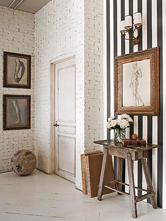 Textured, aged white brick, rustic table and diagonal planked floor, mixed with elegant picture frames and wall sconce, black and white art, then punched up with strategically placed black and white striped wall. Interesting and beautifully put together.