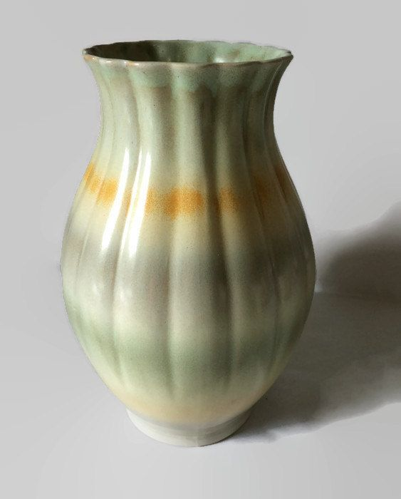 This vase is in pastel hues of greys and creams with a band of burnt orange. The…