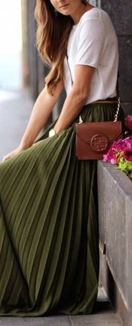 A woman is wearing an olive green maxi skirt and a white t-shirt