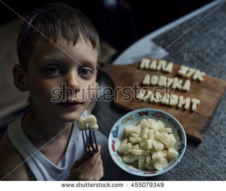 little boy teaches letters and eats pasta