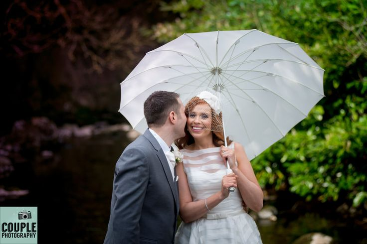 The rain doesn't bother the loved up couple. Weddings at Kinnitty Castle photographed by Couple Photography.