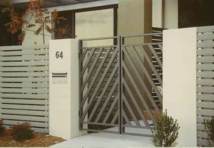 I really like this simple front gate design. I love the recent trend of sturdy cement columns connected by simple metal fencing, and I think the slate on either side of this example look really nice. And the wrought iron gate is open much more than the fence itself, giving you a much better ability to see through it.