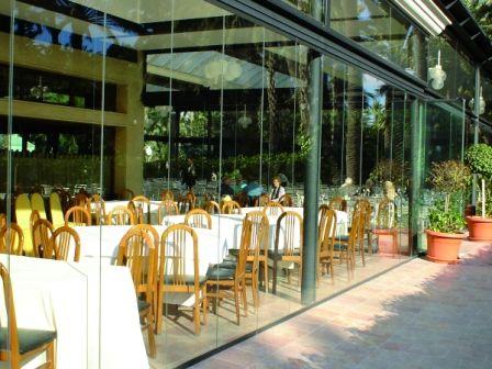 Летняя веранда ресторана за безрамным остеклением. Стекла сдвигаются одним движением руки, закрывая столики от порывистого ветра, мусора или дождя.  #lumon#остекление#ресторан#веранда#стекло