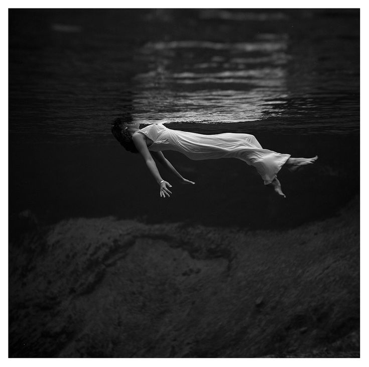 An underwater view of a woman, wearing a long gown, floating in water.— Photograph by World War II and fashion photographer Toni Frissell at Weeki Wachee Springs, Florida, USA, 1947