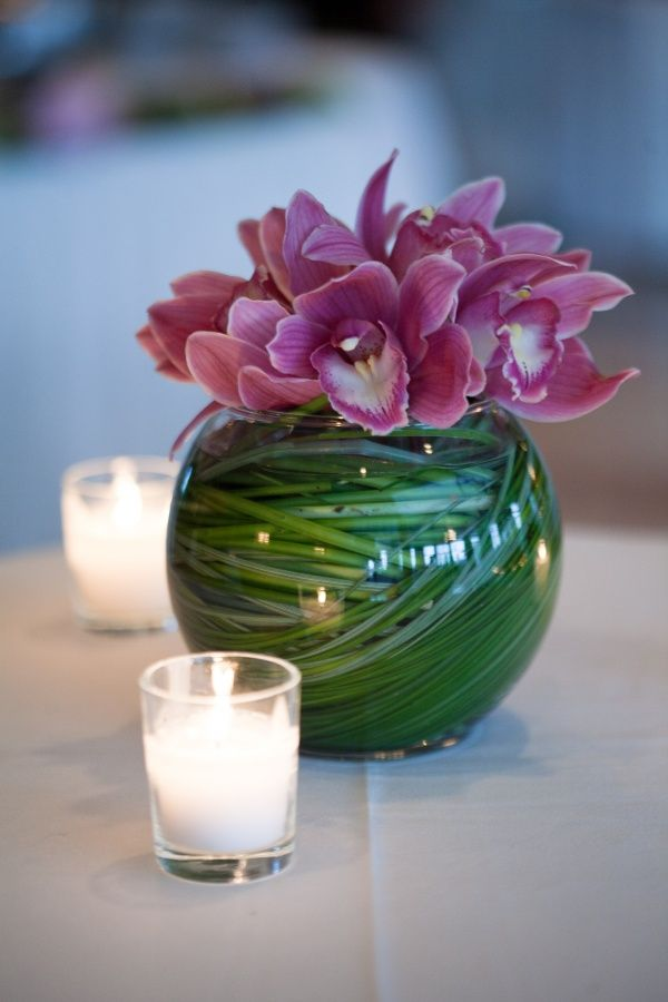 Cocktail table decor- with grass topped with orchids