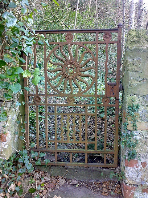 Ornate long disused cast iron gate on a quiet side