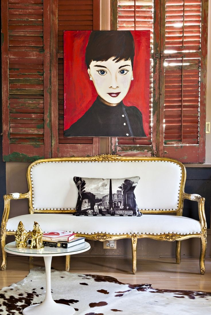 Brass Accents | Rue...red painting of Audrey and the brass trimmed white settee....pulled together by a hide and wooden shutters....