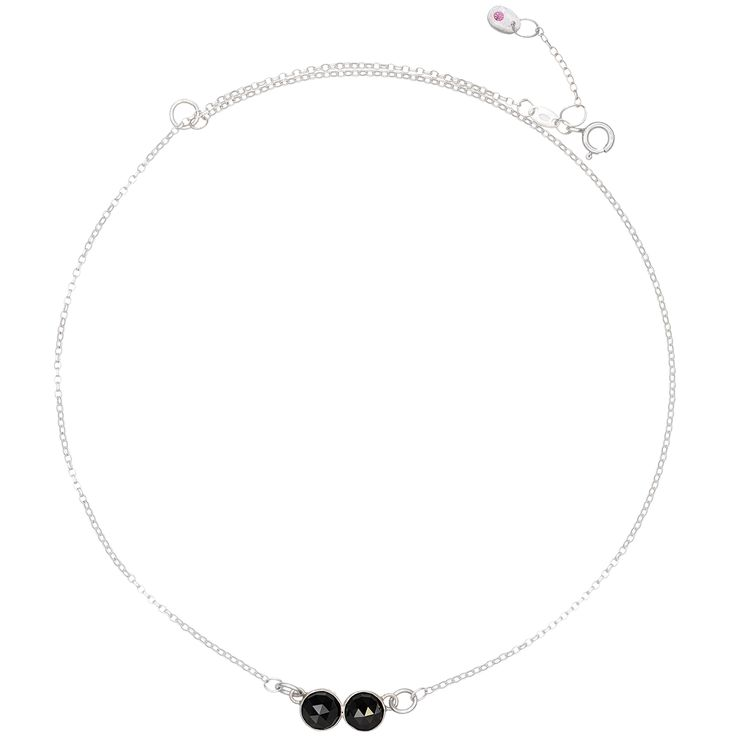 "Two velvet black spinels adorn this simple but powerful gemstone necklace. The rose cut stones are a substantial size and they reflect light on their triangular facets. The side-by-side stones look classy, simple and out of the ordinary. Finished with our fine silver charm with a sparkly 2mm pink garnet. Wear the necklace with a matching ring from the ""Two"" collection."