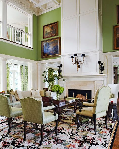 A floral rug grounds the two-story living room and towering mantel, brought to life by vibrant green walls and upholstery - Traditional Home® / Design: Jack Fhillips / Photo: Robert Brantley