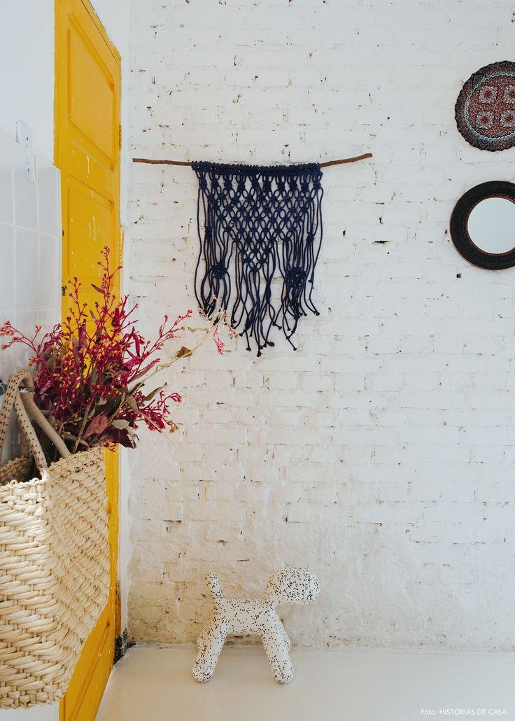 Porta amarela e parede de tijolinho recheada de objetos como pratos e macramê.