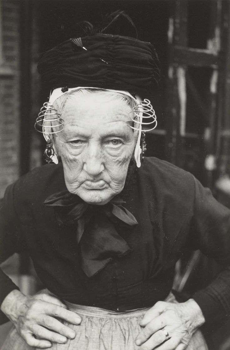 Maria van der Zwan-Moerman in Vlaardingse streekdracht (geboren 1862). Ze is gekleed in zondagse dracht en is in rouw. Ze draagt schootjak met lange schoot, rok en schort zonder 'gatbanden'. Zwarte ondermuts, een zilveren oorijzer met gouden krullen aan de uiteinden en daarover de 'oorijzermuts'. Op de muts is een zwarte kapothoed geplaatst. Aan de krullen hangen zwarte oorijzerhangers. Achter de krullen is een paar rouwspelden in de muts gestoken. 1950 #ZuidHolland #Vlaardingen