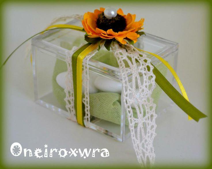Μπομπονιέρα, κουτάκι plexiglass με κίτρινη, χακί και δαντελένια κορδέλα, διακοσμημένη με ηλιοτρόπιο και πέρλα. Στο εσωτερικό περιέχει εκτός από τα κουφέτα πράσινη λινάτσα.