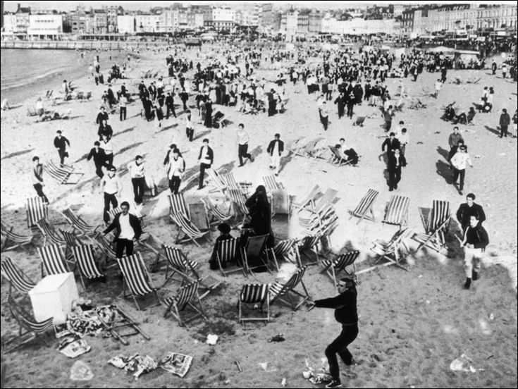 Mods invading the beach at Margate, Kent waving sticks and throwing bottles at retreating Rockers, 18 May 1964. Scores of youths were given prison sentences following a Whitsun weekend of violent clashes between gangs of Mods and Rockers at a number of resorts on the south coast of England. Photo: Keystone/Getty Images