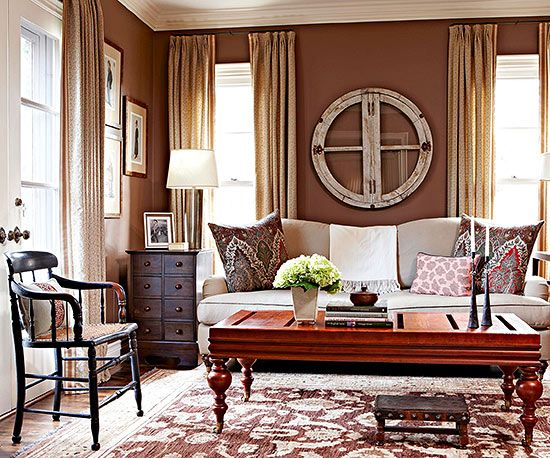 Calculated layers of latte linens and mahogany furniture against mocha walls work together to create an enveloping living room.