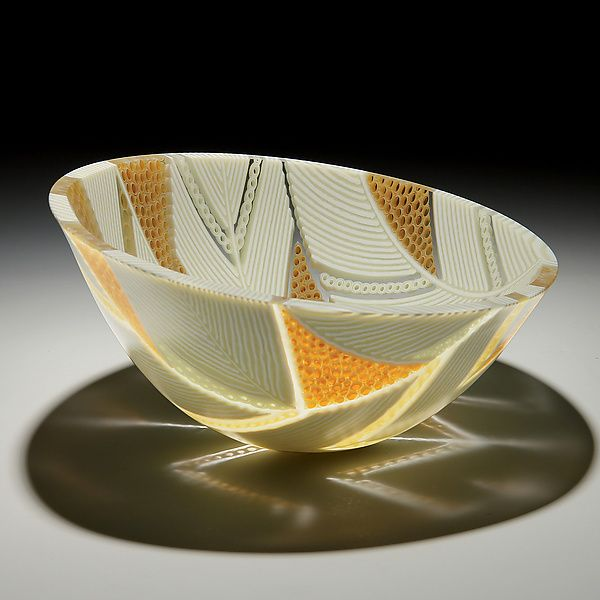 Arrows Bowl in Honey and Cream by Patti & Dave Hegland. Featuring an intricate angular design of cream-colored glass placed on edge, this sculptural piece incorporates segments of hand-pulled murrini in cream, ambers, and clear to form a balanced vessel. The detail is enhanced by the vessel's satin interior. The strong geometry and structure of this work is inherent in the strip construction approach used to create it. Large sheets of glass are cut into narrow strips, laid on edge, an...