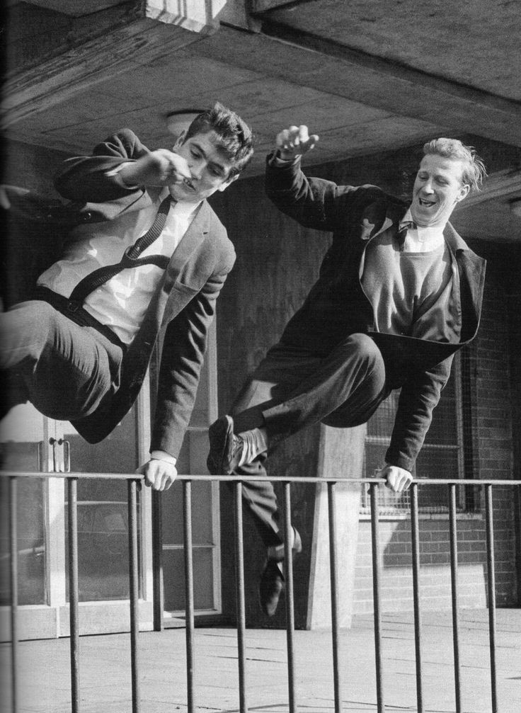Footballers Norman Hunter and Jack Charlton hurl over railings outside Elland Road stadium in celebration after being selected in England's 1966 World Cup squad.