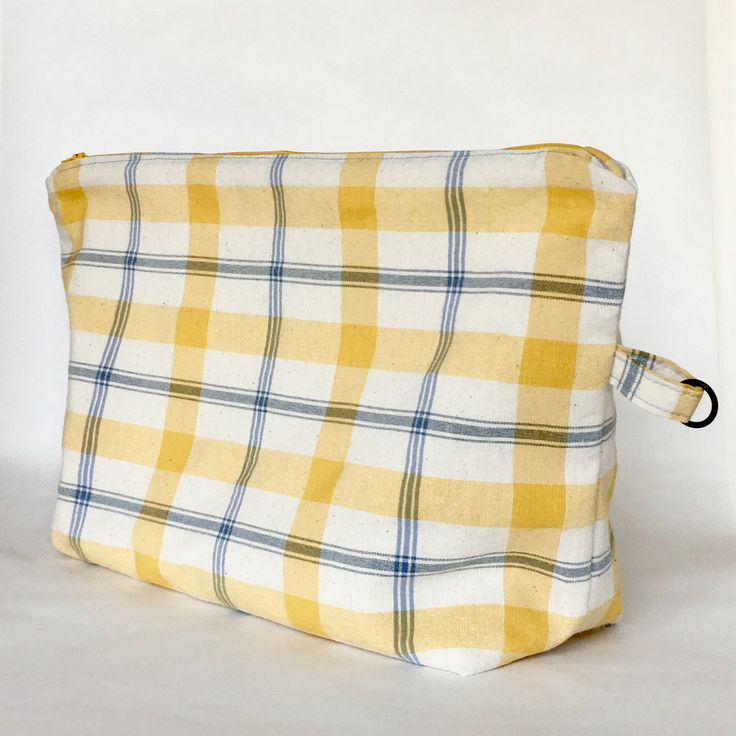 Traditional sweater size wedge project bag with zipper closure.  Sporting a sunny woven plaid fabric, this project bag is roomy with plenty of pockets and a ring to carry your accessories.  Check it out at QuiltMoxie.Etsy.com .