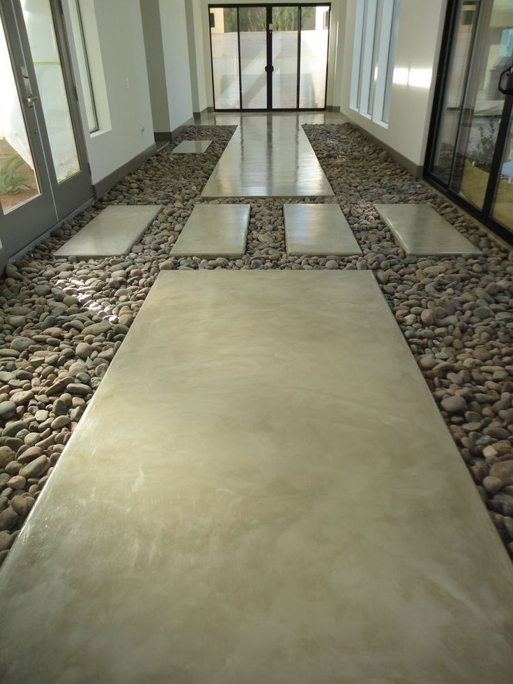 Seamless paving coated with SEMCO seamless stone in a modern concrete look combined with pebbles.