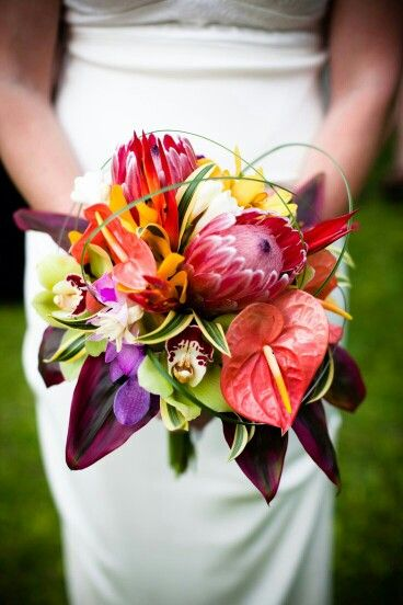 Exotic & Glamorous Bride's Bouquet Comprised Of: Pink/Yellow Anthurium, Pink Queen Protea, White Florals, Yellow Orchids, Green Cymbidium Orchids, Purple Dendrobium Orchids, Purple Callas, Green Lily Grass + Additional Greenery/Foliage